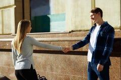 O par feliz, sorrindo, uma menina guarda a mão de um indivíduo e de chamadas para ele, trações, ligações fotografia de stock royalty free