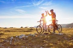 O par feliz vai em uma estrada asfaltada da montanha nas madeiras em bicicletas com os capacetes que dão-se uns cinco altos fotografia de stock