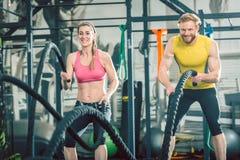 O par forte que exercita junto com a batalha ropes durante o treinamento funcional foto de stock