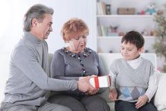 O par idoso dá um presente a seu neto em seu aniversário foto de stock royalty free