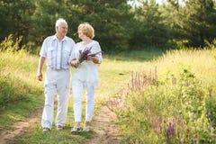 O par idoso no vestido de linho branco que anda fora, olhar em se o ` s eyes, nas mãos um ramalhete das flores foto de stock royalty free