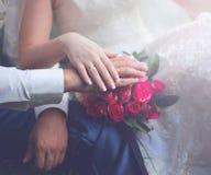 O par macio do casamento, mãos dos noivos, ramalhete delicado cor-de-rosa floresce foto de stock royalty free