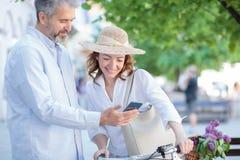 O par maduro feliz que anda em torno da cidade, mulher est? empurrando uma bicicleta fotografia de stock