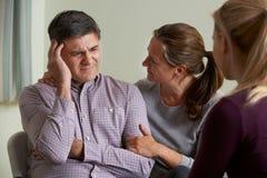 O par maduro que fala com o conselheiro como a mulher consola o homem imagens de stock royalty free