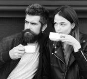 O par no amor bebe o café durante a ruptura de café Bebida quente e datar A menina e o indivíduo farpado têm o café Fotografia de Stock Royalty Free