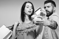 O par no amor guarda o cartão de crédito no fundo cinzento fotografia de stock royalty free