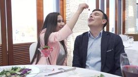 O par no amor na ceia do restaurante, uma menina está alimentando a um indivíduo um vídeo da metragem do estoque da baga filme