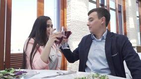 O par no amor no restaurante bebe um vinho tinto para a fraternidade e beija o vídeo conservado em estoque da metragem vídeos de arquivo