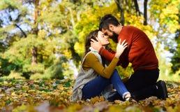 O par no amor que senta-se no outono caído sae foto de stock royalty free