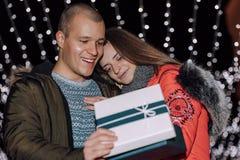 O par novo abre junto a caixa com um presente imagens de stock royalty free
