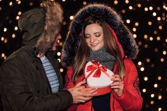 O par novo abre junto a caixa com um presente na noite do inverno imagem de stock