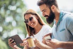 O par novo alegre que senta-se em um banco de parque e usa uma tabuleta digital fotografia de stock
