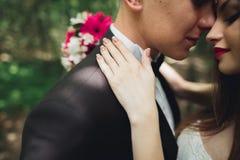 O par novo bonito do casamento é de beijo e de sorriso no parque Imagens de Stock