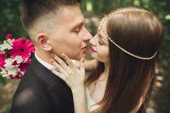 O par novo bonito do casamento é de beijo e de sorriso no parque Fotografia de Stock Royalty Free