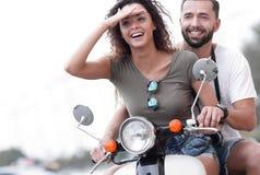 O par novo bonito está sorrindo ao montar um 'trotinette' imagens de stock royalty free
