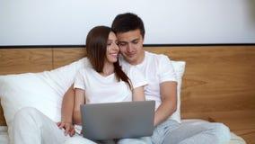 O par novo bonito está usando o portátil e está sorrindo ao encontrar-se na cama em casa video estoque