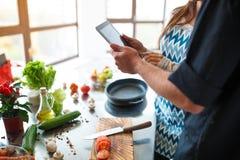 O par novo bonito usa uma tabuleta digital ao cozinhar o alimento na cozinha em casa fotografia de stock