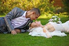 o par Novo-casado encontra-se em uma grama Fotos de Stock Royalty Free