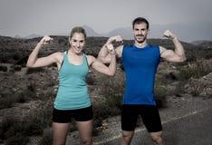 O par novo do esporte que levanta e que mostra arma o sorriso dos músculos do bíceps feliz fotografia de stock