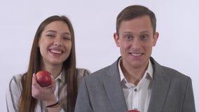 O par novo do retrato ascendente próximo que come maçãs vermelhas, mulher está dançando, indivíduo tão feliz e sorriso isolada no vídeos de arquivo