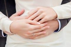 O par novo guarda uma mão em uma mão com um fim da aliança de casamento Fotografia de Stock