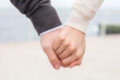 O par novo guarda uma mão em uma mão com um fim da aliança de casamento Foto de Stock