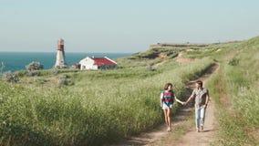 O par novo romântico anda as mãos holging junto, falando e rindo na fuga da areia perto do farol no penhasco do litoral filme