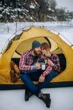 O par novo senta-se na barraca e bebe-se o chá quente durante a caminhada do inverno imagens de stock