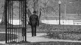 O par que anda no parque durante as agitações de neve, preto e branco, suporta à câmera imagem de stock royalty free