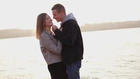 O par romântico feliz está nos abraços no por do sol, menina dos beijos do homem filme