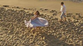 O par romântico novo - menina beautyful na luz longa - vestido cor-de-rosa dança no Sandy Beach para seu noivo Momento apaixonado filme