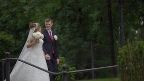 O par surpreendente de recém-casados no amor está falando felizmente ao andar ao longo do jardim de florescência filme