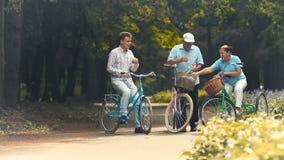 O par velho tem um resto e bebe a água ao montar em bicicletas no parque video estoque
