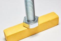 O parafuso do metal com mentiras da linha em uma barra de madeira fotos de stock