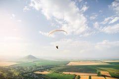 O paraglider profissional em um terno do casulo voa altamente acima da terra contra o céu e dos campos com montanhas fotografia de stock