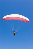 O Paraglider voa no azul Fotos de Stock