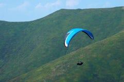 O Paraglider voa sobre um vale da montanha em um dia de verão ensolarado Parapente nos Carpathians no verão imagem de stock