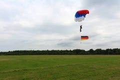 O paraquedista está aterrando com bandeira alemão imagem de stock