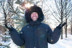 O Parka encapuçado vestindo de sorriso da pele do homem reveste no parque do inverno foto de stock