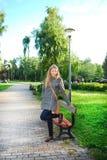 O parque é uma menina que descansa seu pé no banco. Imagens de Stock