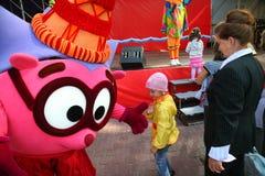 O parque da cidade do animador do ator no herói Smeshariki engraçado dos desenhos animados da boneca do traje mante distraído cri Imagens de Stock