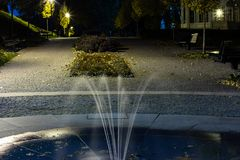O parque da cidade no cenário da noite com um lugar para descansar a paisagem da cidade da noite estaciona na primavera Bancos, t fotos de stock