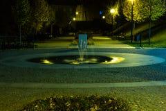 O parque da cidade no cenário da noite com um lugar para descansar a paisagem da cidade da noite estaciona na primavera Bancos, t foto de stock royalty free