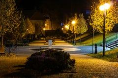 O parque da cidade no cenário da noite com um lugar para descansar a paisagem da cidade da noite estaciona na primavera Bancos, t foto de stock
