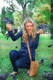 O parque, os pombos de alimentação da menina Fotos de Stock