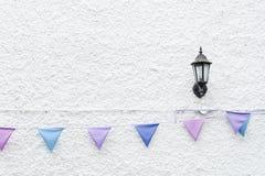 O partido colorido embandeira a estamenha que pendura no fundo branco da parede com luz da lâmpada de parede Projeto mínimo do es Fotografia de Stock