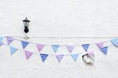 O partido colorido embandeira a estamenha que pendura no fundo branco da parede com luz da lâmpada de parede Projeto mínimo do es Fotos de Stock