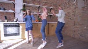 O partido da família, mãe alegre com filhas dança e o divertimento passa o tempo na cozinha em casa
