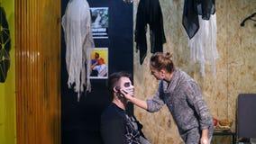 O partido de Dia das Bruxas, artista de composição tira uma composição terrível na cara de um homem para um partido de Dia das Br filme