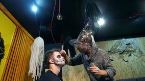 O partido de Dia das Bruxas, artista de composição tira uma composição terrível na cara de um homem para um partido de Dia das Br video estoque